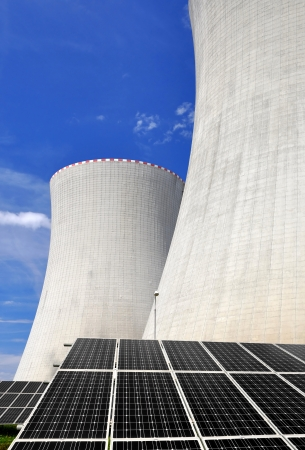 outdoor electricity: Solar energy panels before a nuclear power plant  Stock Photo