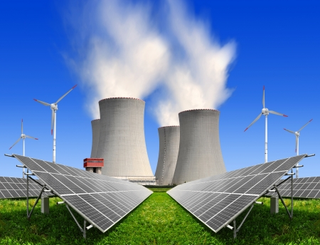 Alternativ: Solar energy panels before a nuclear power plant and wind turbines Stock Photo