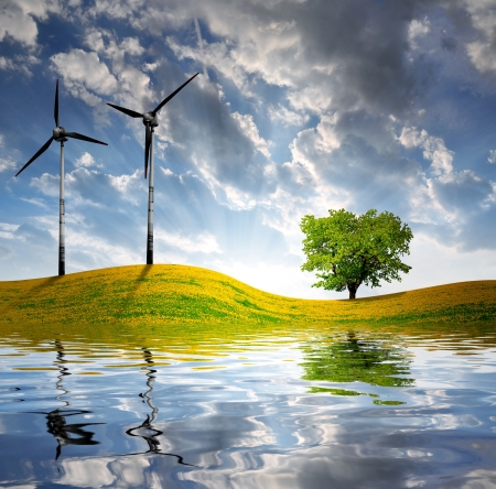 environmentally friendly: sunset over meadow with wind turbines Stock Photo
