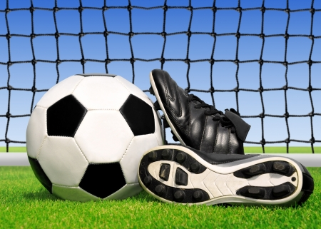 soccer ball and shoes in grass photo