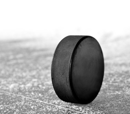 ice surface: black hockey puck on ice rink  Stock Photo