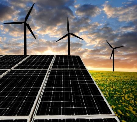 Des panneaux solaires et des éoliennes dans le soleil couchant