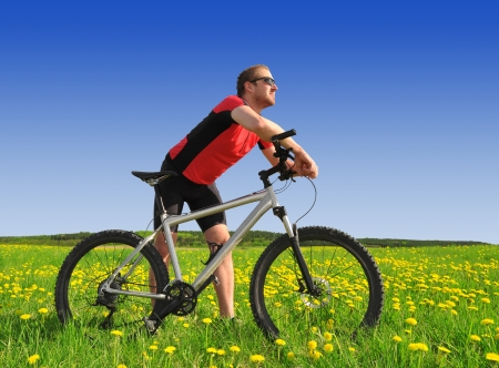 biker with the mountain bike in the dandelion field  photo