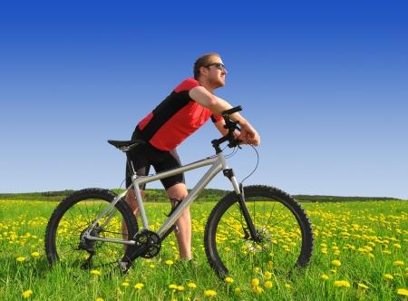 promptness: biker with the mountain bike in the dandelion field