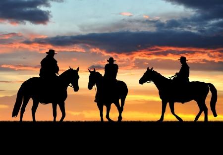 silueta ciclista: Silueta de los vaqueros con caballos en la puesta del sol
