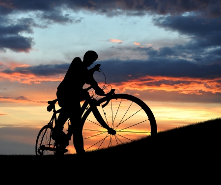 cycling helmet: silhouette of the cyclist on road bike at sunset