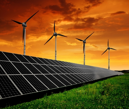 energia solar: Paneles de energía solar con turbinas de viento en la puesta del sol
