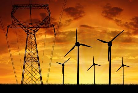 recursos naturales: Las turbinas de viento con la línea eléctrica en la puesta del sol