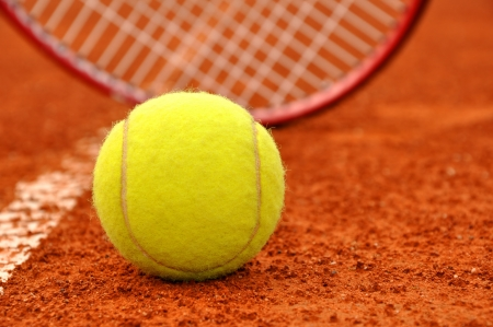 Tennis ball and racket on the court photo
