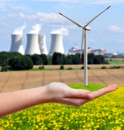 nuclear energy: wind turbine in hand on the background nuclear power plant Stock Photo