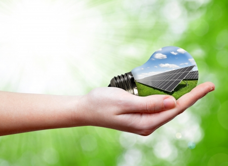 outdoor electricity: Bulb with of solar panel in hands Stock Photo