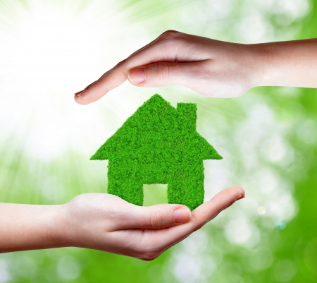 real estate agency: green house in hands Stock Photo