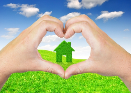 heart from hands  In the background Green grass house symbol photo