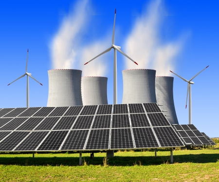 Solar energy panels before a nuclear power plant and wind turbines photo
