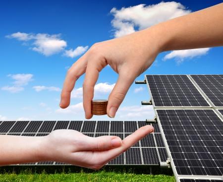 erneuerbar: Weibliche Hände mit Geld im Hintergrund Solar-Panel Lizenzfreie Bilder
