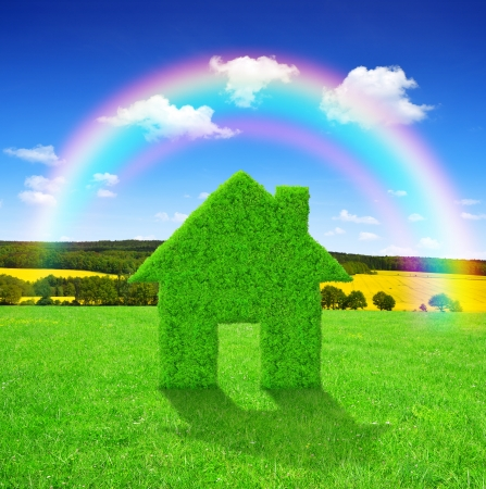 Green grass house symbol with rainbow on meadow