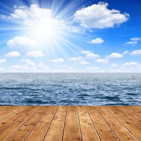 insolación: Tarima de madera en el fondo del cielo soleado sobre el mar
