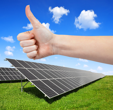 Solar energy panels and hand with thumb up  photo