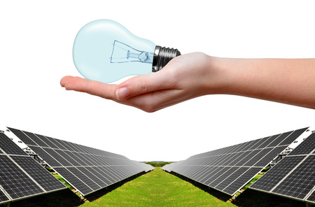 electrical energy: Solar energy panels and bulb in hand on white background