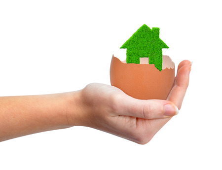company ownership: hand holding green house in eggshell isolated on white Stock Photo