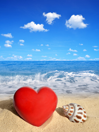 heart in sand: Conch shell with heart on beach Stock Photo