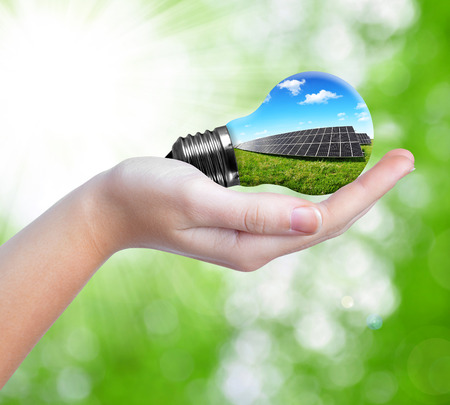Bulb with of solar panel in hand photo