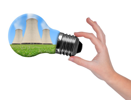 nuclear plant: Hand holding bulb with nuclear power plant isolated on white