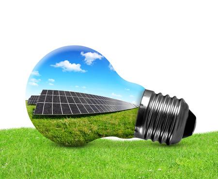Solar panels in light bulb on white background. Green energy concept.  photo