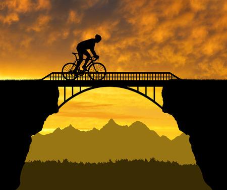 Cyclist riding across the bridge at sunset Stock Photo