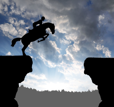 silhouette of a rider on a jumping horse photo