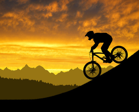 minded: silhouette of the cyclist on downhill bike at sunset