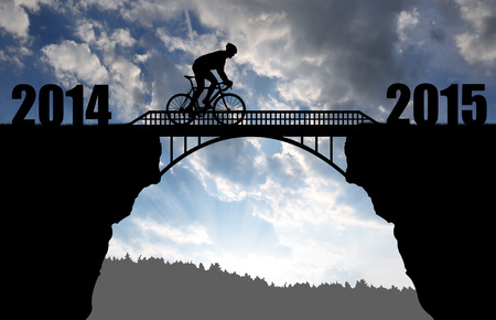 rapidity: Cyclist riding across the bridge at sunset .Forward to the New Year 2015