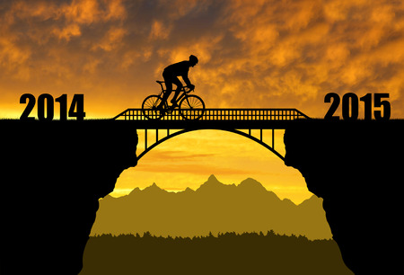 footbridge: Cyclist riding across the bridge at sunset .Forward to the New Year 2015