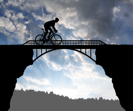 rapidity: Cyclist riding across the bridge at sunset Stock Photo