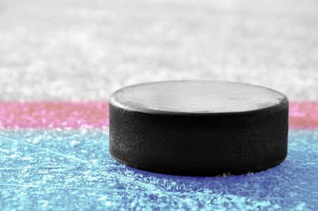 ice surface: black hockey puck on ice rink