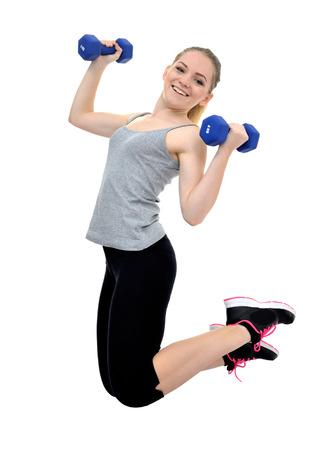 Feliz niña saludable y activo salta con pesas aislados sobre fondo blanco