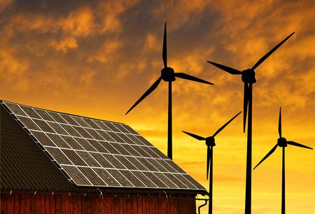 El panel solar en el techo de la casa en las turbinas de viento en la puesta de sol de fondo.
