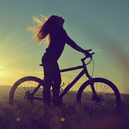 girl on a bicycle in the sunset photo