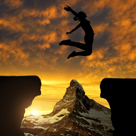 cliff jumping: Silhouette girl jump through the gap at sunset. In the background Matterhorn.