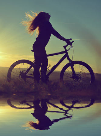 Girl on a bicycle in the sunset reflected on the water surface photo