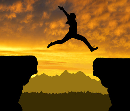 cliff jumping: Silhouette girl jump through the gap at sunset. Stock Photo