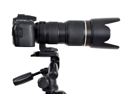 telezoom: DSLR camera with zoom lense on a tripod isolated