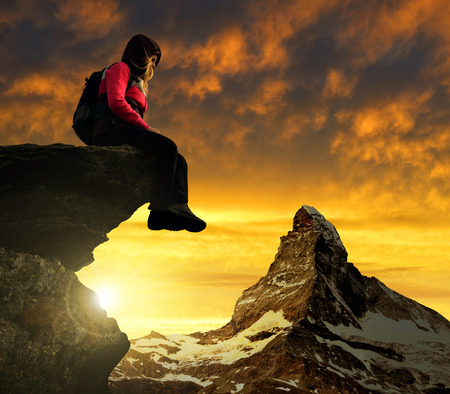 Girl sitting on a rock, in the background mount Matterhorn at sunset Swiss Alps, Europe photo