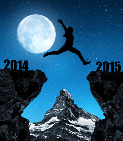 Girl jumps to the New Year 2015 in the background mount Matterhorn photo