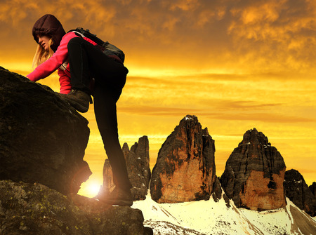 dolomite: Girl on rock, in the background Tre Cime di Lavaredo at sunset ,Dolomite Alps, Italy Stock Photo