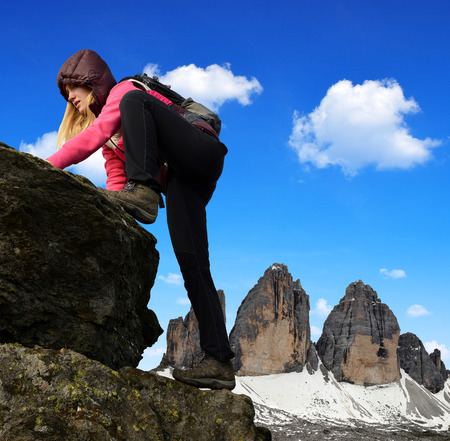 Girl on rock, in the background Tre Cime di Lavaredo, Dolomites, Italy photo