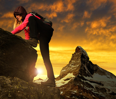 Girl on rock, in the background mount Matterhorn at sunset Swiss Alps, Europe photo