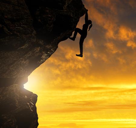climber: Silhouet van meisje klimmen op de rots bij zonsondergang