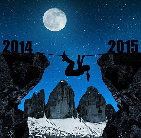 Girl climbs into the New Year 2015. In the background Tre cime di Lavaredo, Dolomite Alps, Italy photo