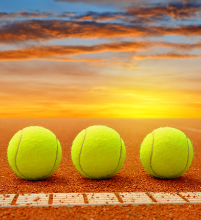 tennis clay: Tennis balls on a tennis clay court in the sunset